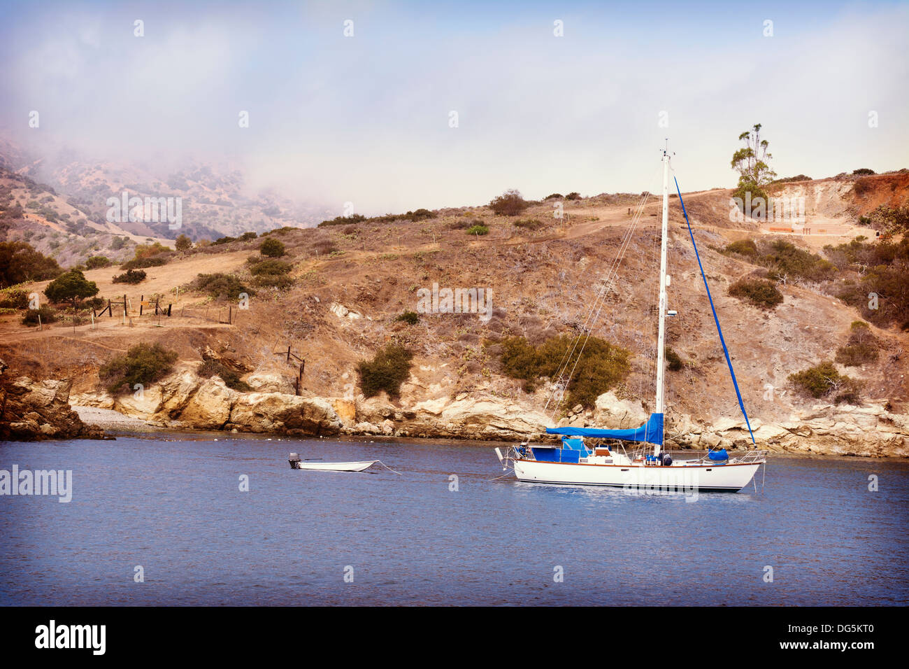 A sailboat and dingy anchored in a bay at Catalina Island. - Stock Image