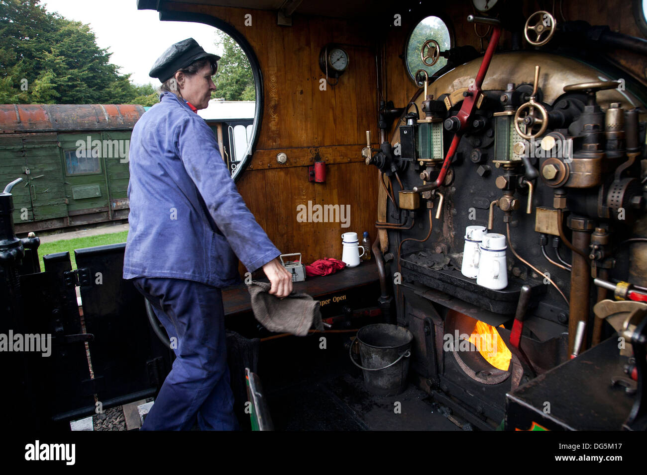 A female engine driver working the footplate of a steam locomotive on the heritage Bluebell railway line. - Stock Image