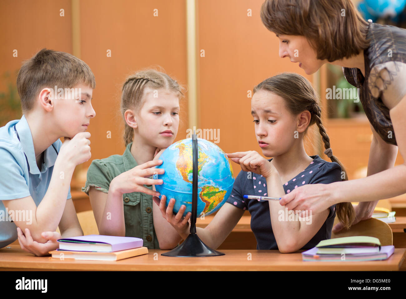 school kids studying a globe together with teacher - Stock Image