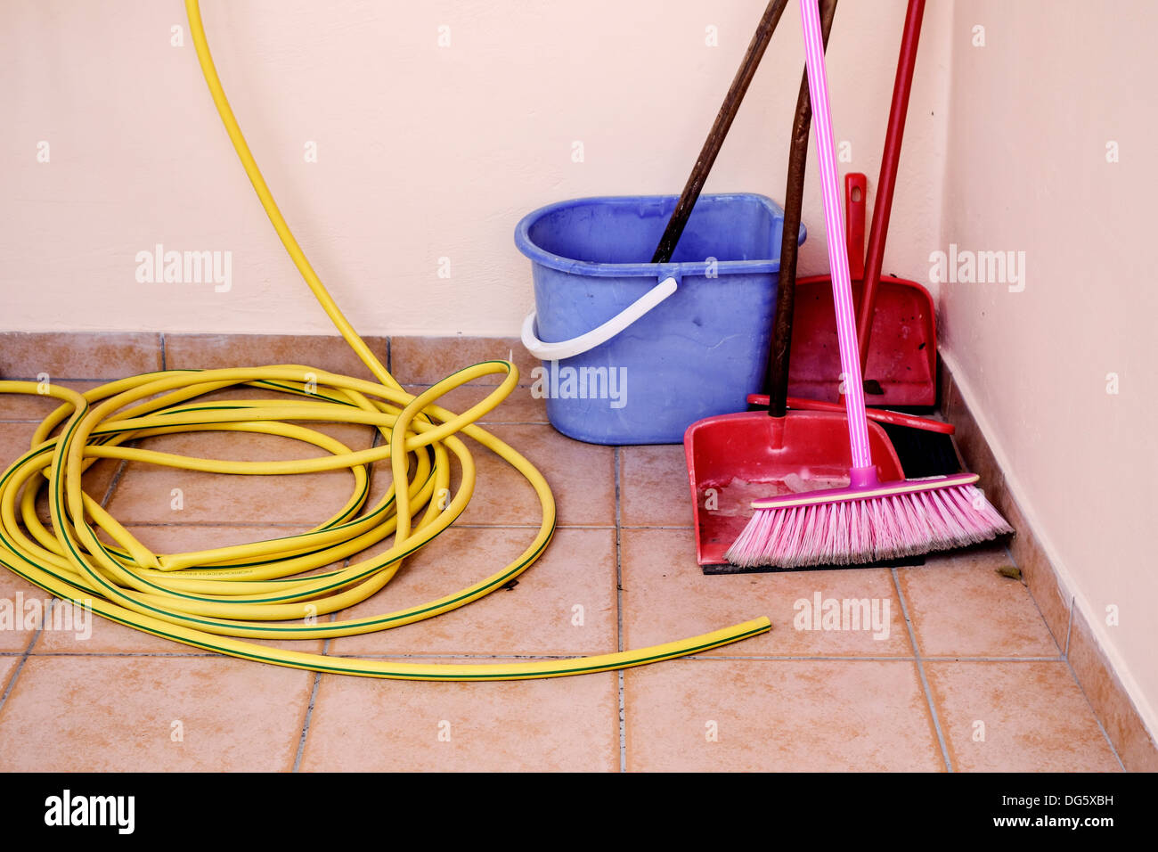 Household Cleaning Utensils and Hosepipe. - Stock Image