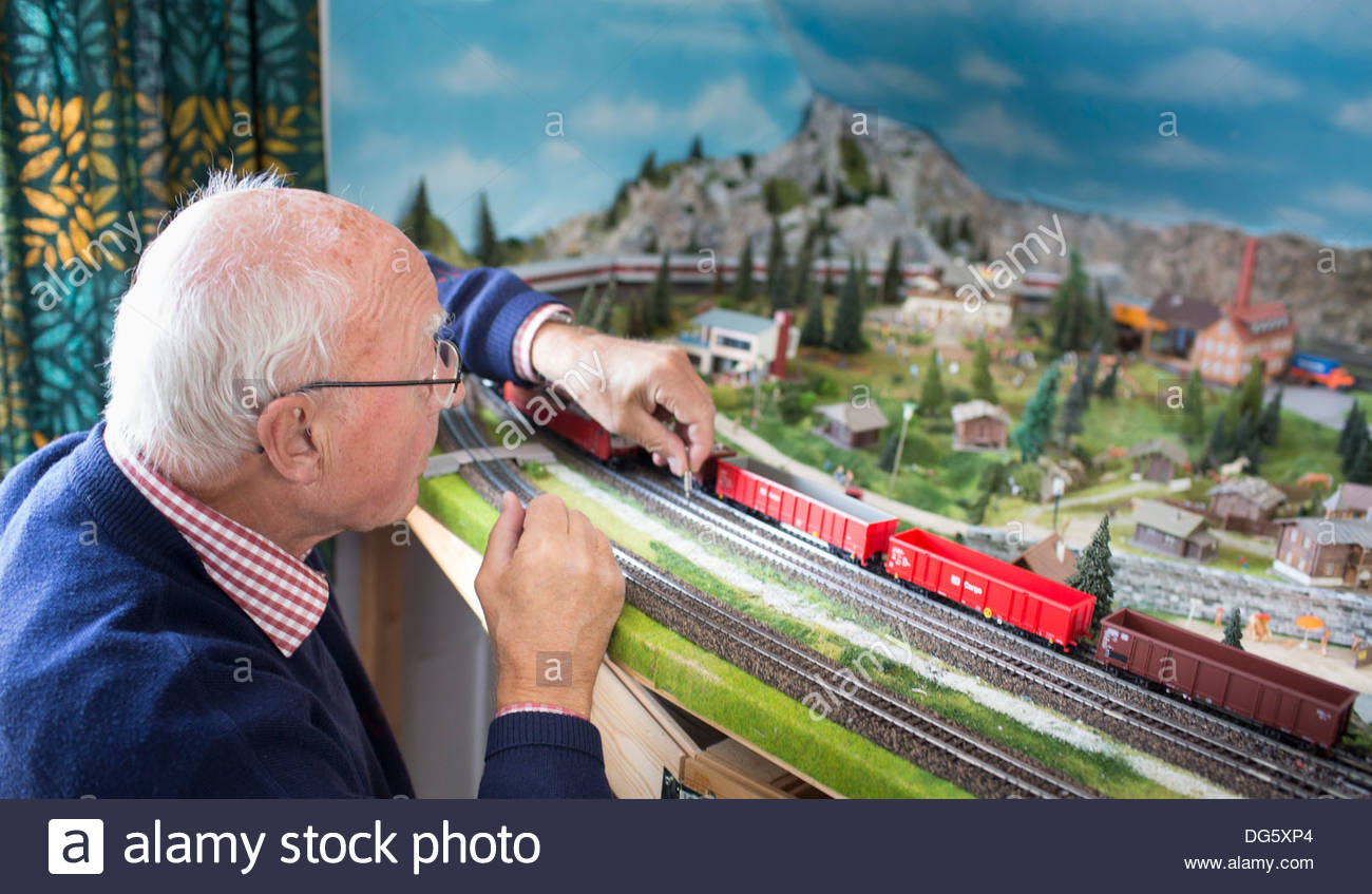 Senior man playing with toy train Stock Photo