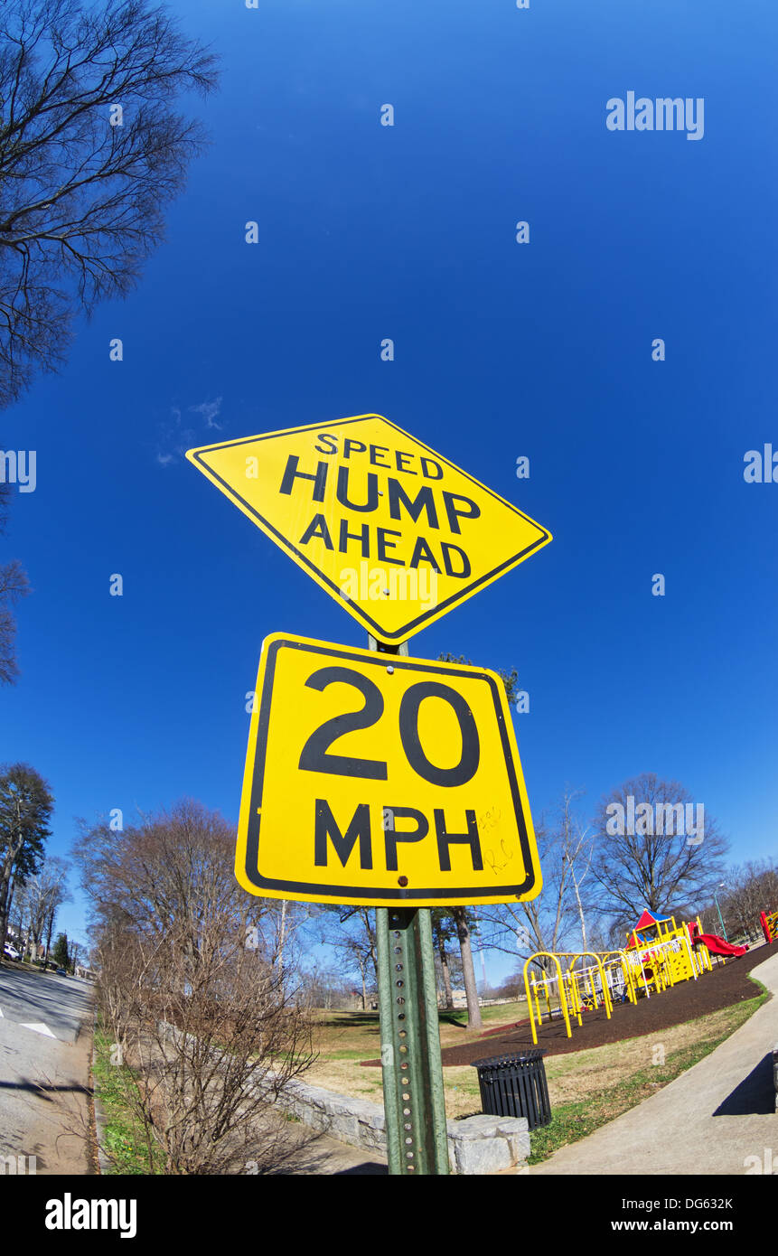 fisheye image of speed hump ahead sign with playground - Stock Image