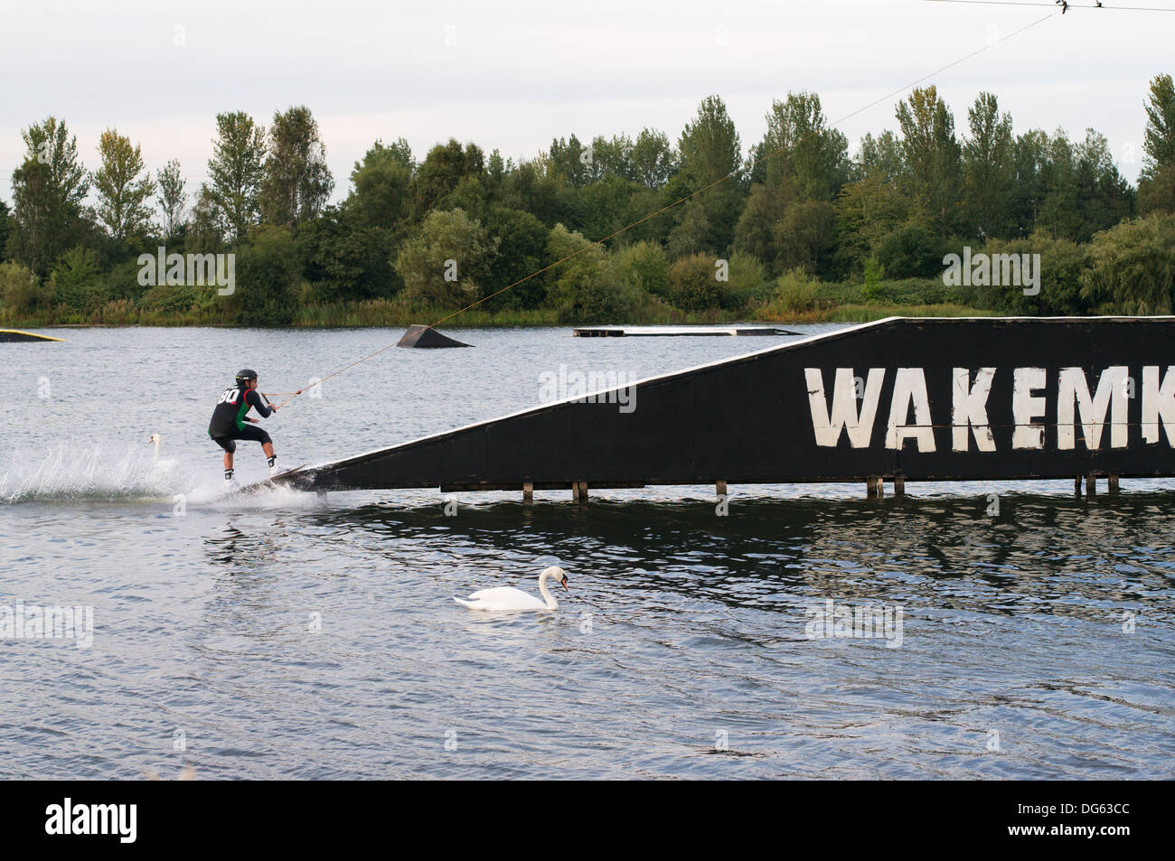 A wakeboarder about to ascend a ramp at the WAKEMK cable wakeboard and waterski centre Milton Keynes, England UK - Stock Image