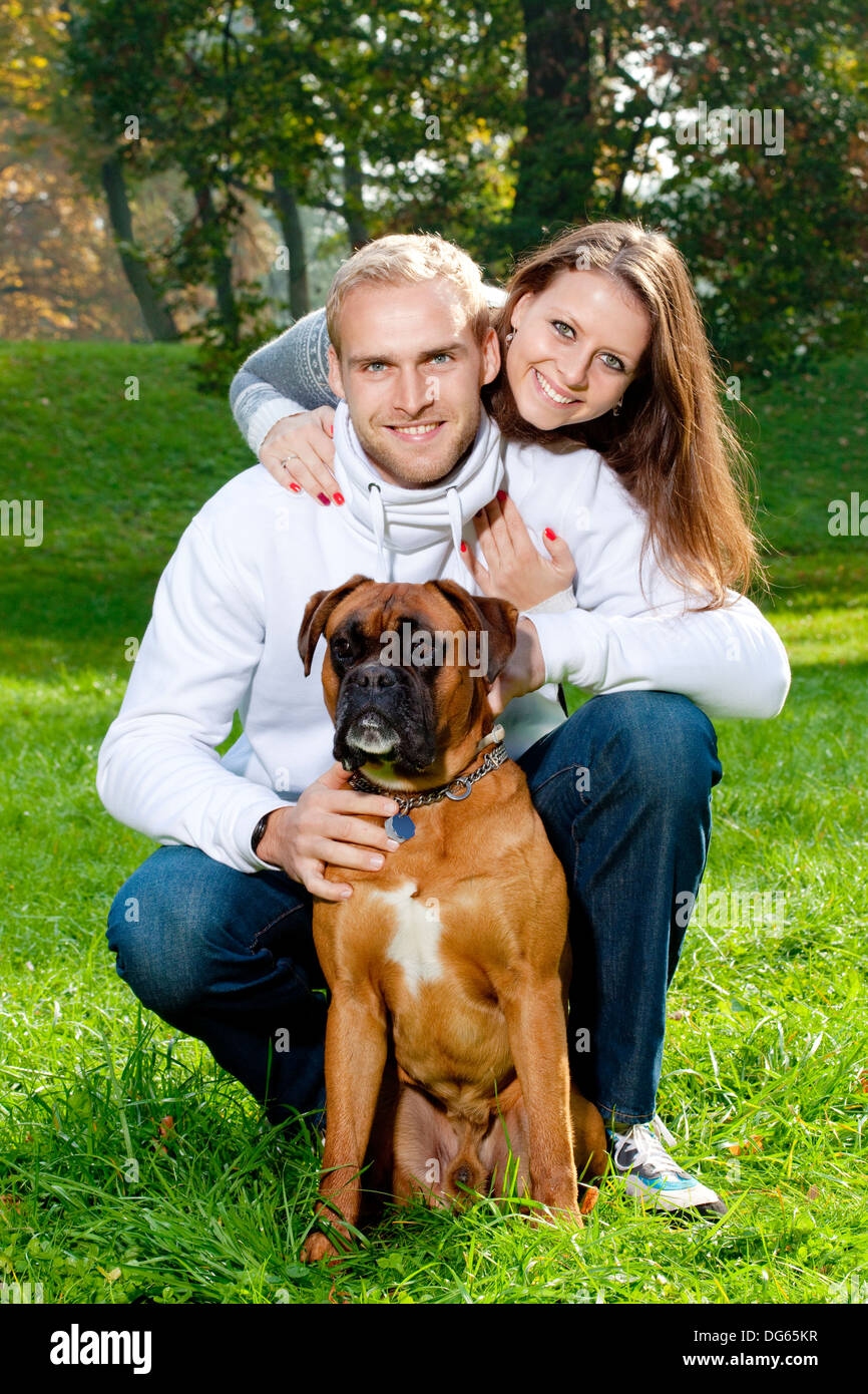 portrait of a happy young couple with their dog in the park. - Stock Image