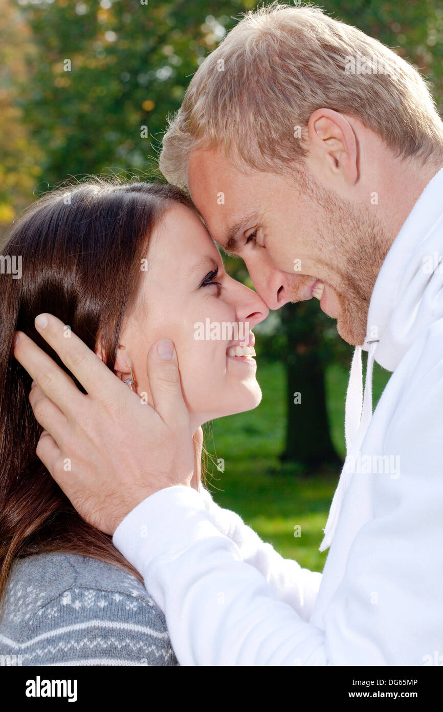 portrait of a happy young couple in the park, embracing, smiling. - Stock Image