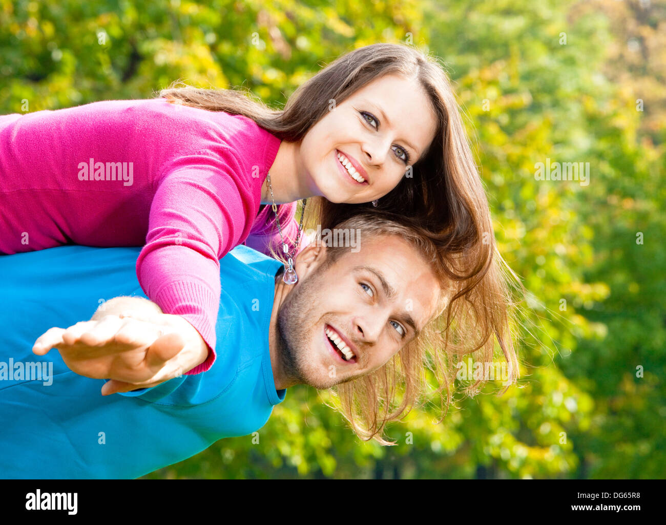 happy young couple piggybacking, arms outstretched, smiling. - Stock Image