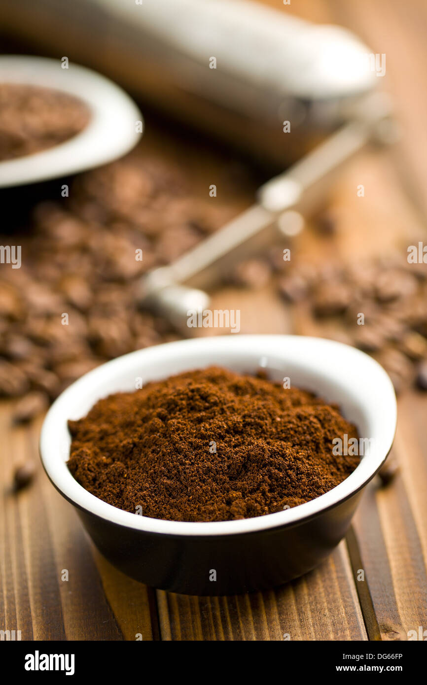 ground coffee in ceramic bowl on wooden table - Stock Image