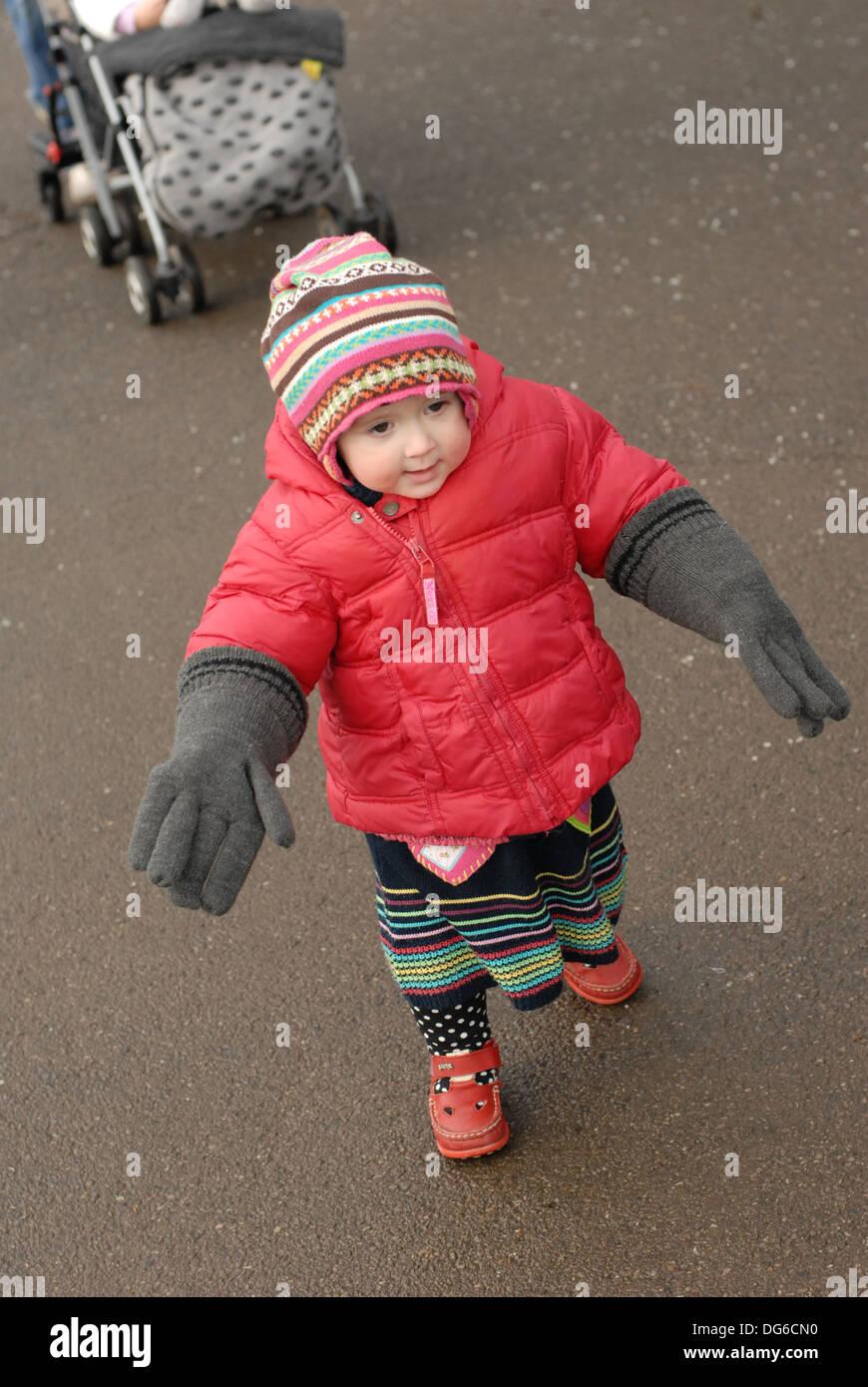Toddler walking wearing adult gloves - Stock Image