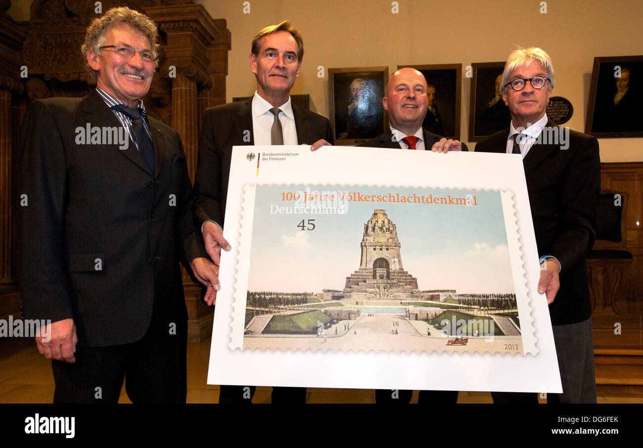 Chairman of the support association Monument to the Battle of the Nations e.V., Klaus-Miachel Rohrwacher (L-R), mayor of Leipzig Burkhard Jung (SPD), parliamentary permanent secretary with the German Minister of Finance, Hartmut Koschyk, and director od te Museum of the History of the City of Leipzig, Volker Rodekamp, pose behind an oversized version of the German special issue stamps '100 Years Monument to the Battle of the Nations' with a nominal value of 0.45 euro at the Old City Hall in Leipzig, Germany, 15 October 2013. The stamp with a historic view of the Monument to the Battle of the N - Stock Image