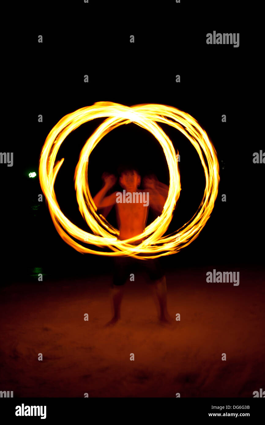 fire dance, male performance fire twirling dance on the island - Stock Image