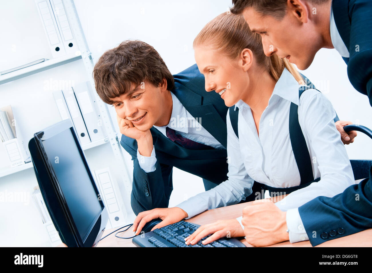 Three young successful businesspeople. Screen has a clipping path. - Stock Image
