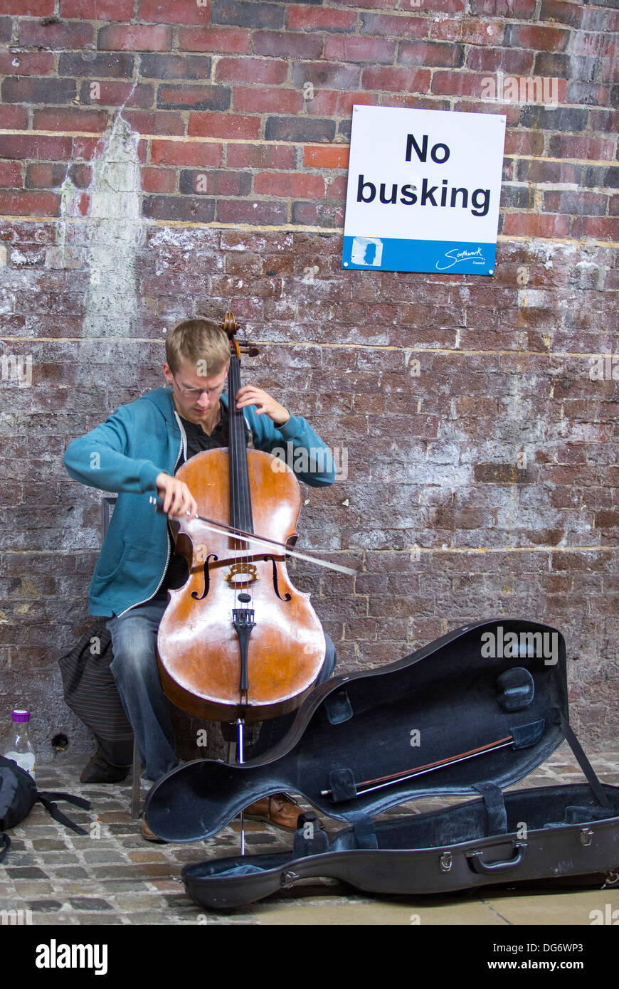 BUSKER PLAYING NEAR A NO BUSKING SIGN - Stock Image