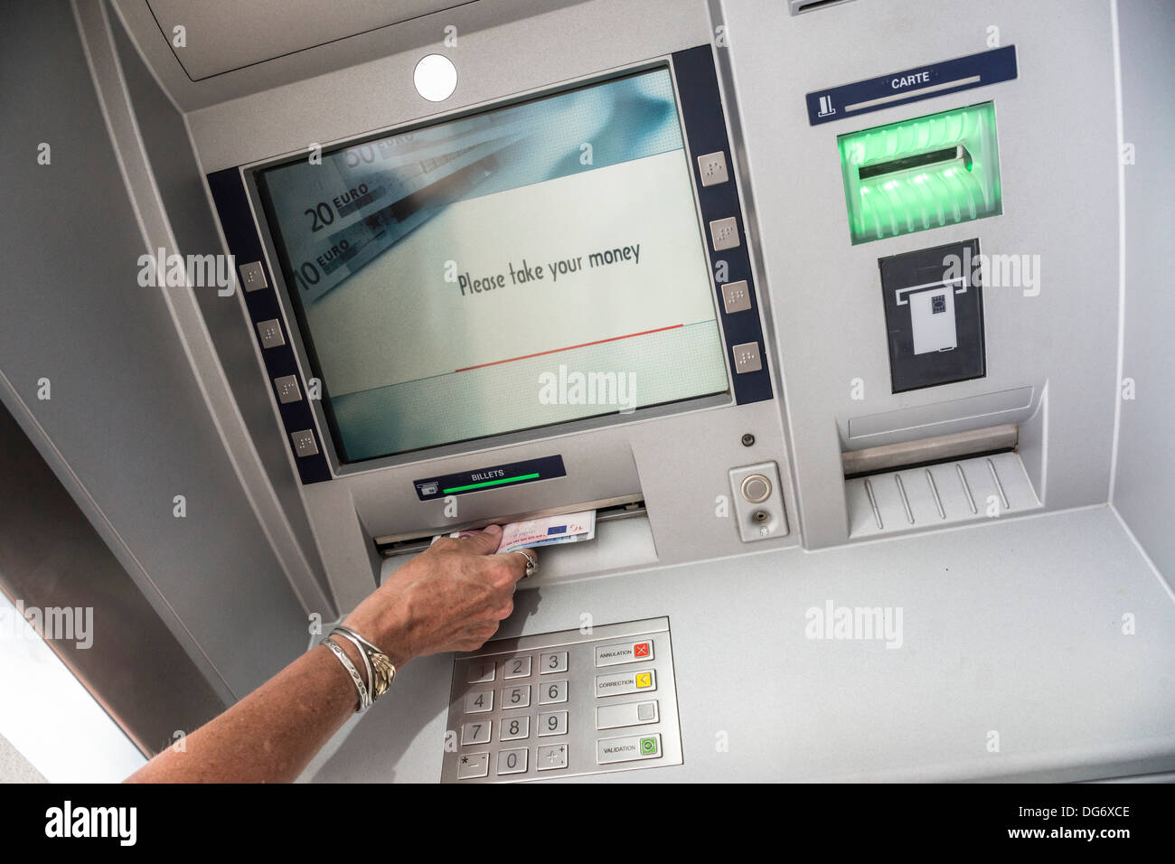 Getting Euro money from an ATM in France. - Stock Image