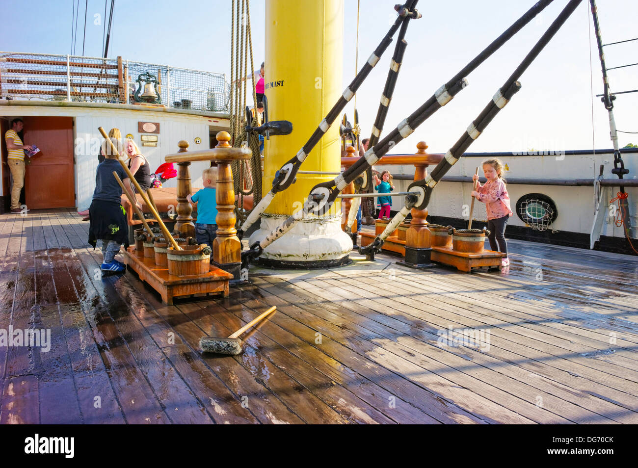 Children visiting the Tall ship Glenlee sample life on board by washing the deck with water and brushes watched by their parents - Stock Image