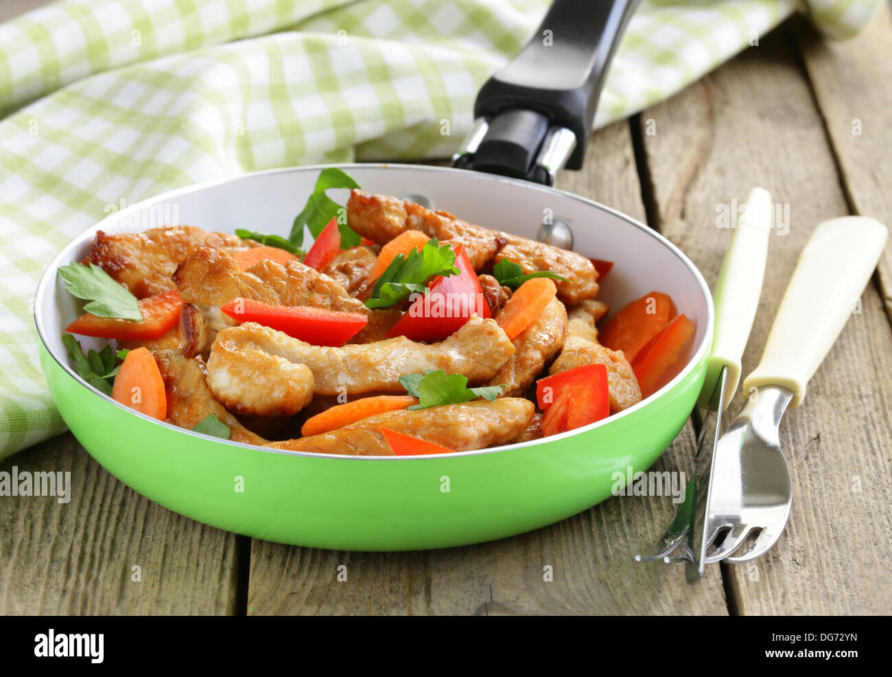 fried chicken (turkey) fillets with vegetables in a pan - Stock Image