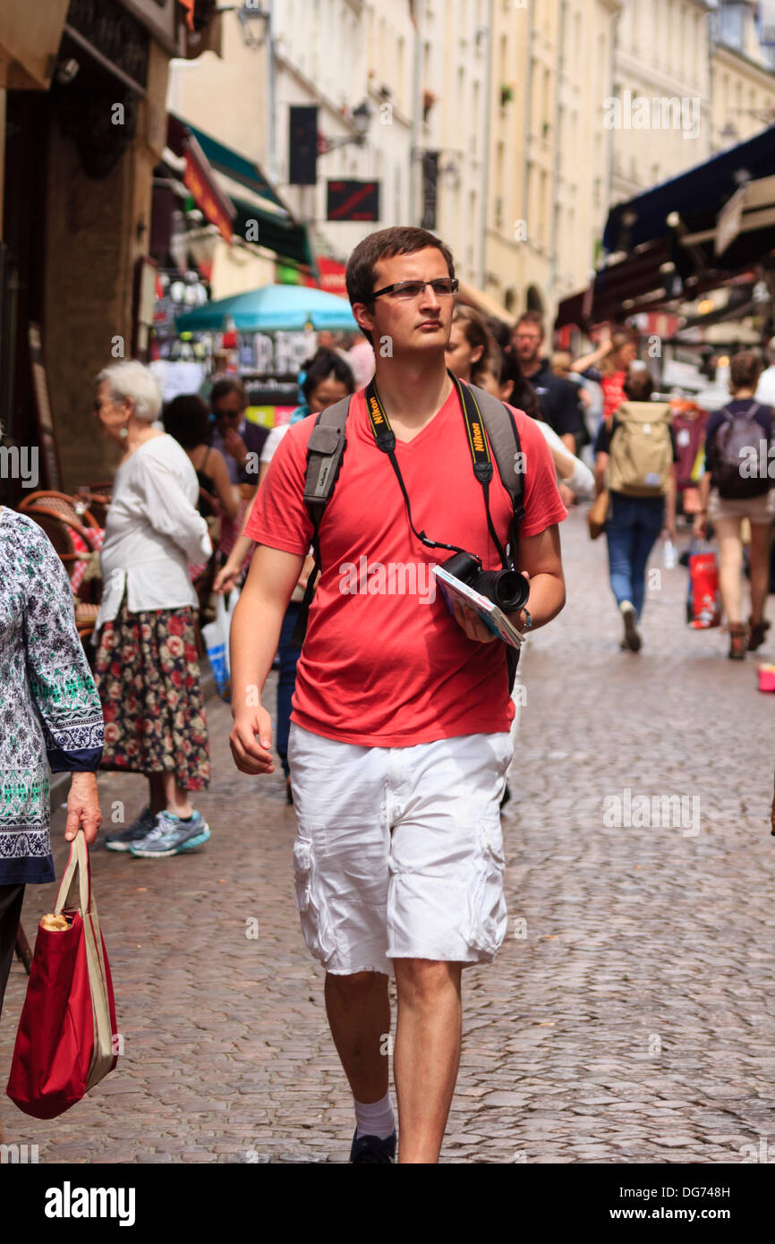Male tourist with body camera is walking through the crowded Mouffetard street in central Paris, France - Stock Image