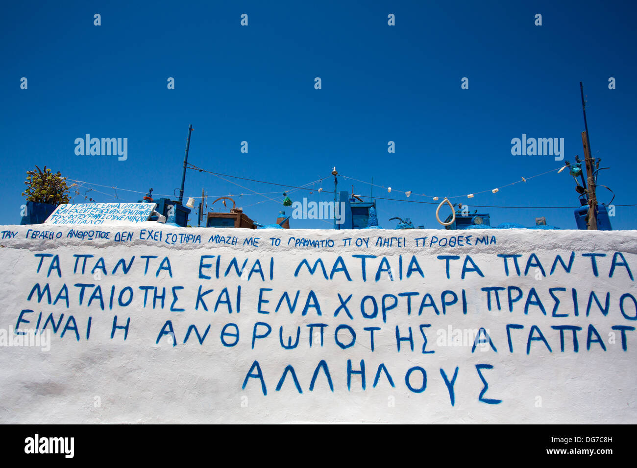 Artistic installation on a  roof of a house in Folegandros, the installation is made of strange objects all painted in blue - Stock Image