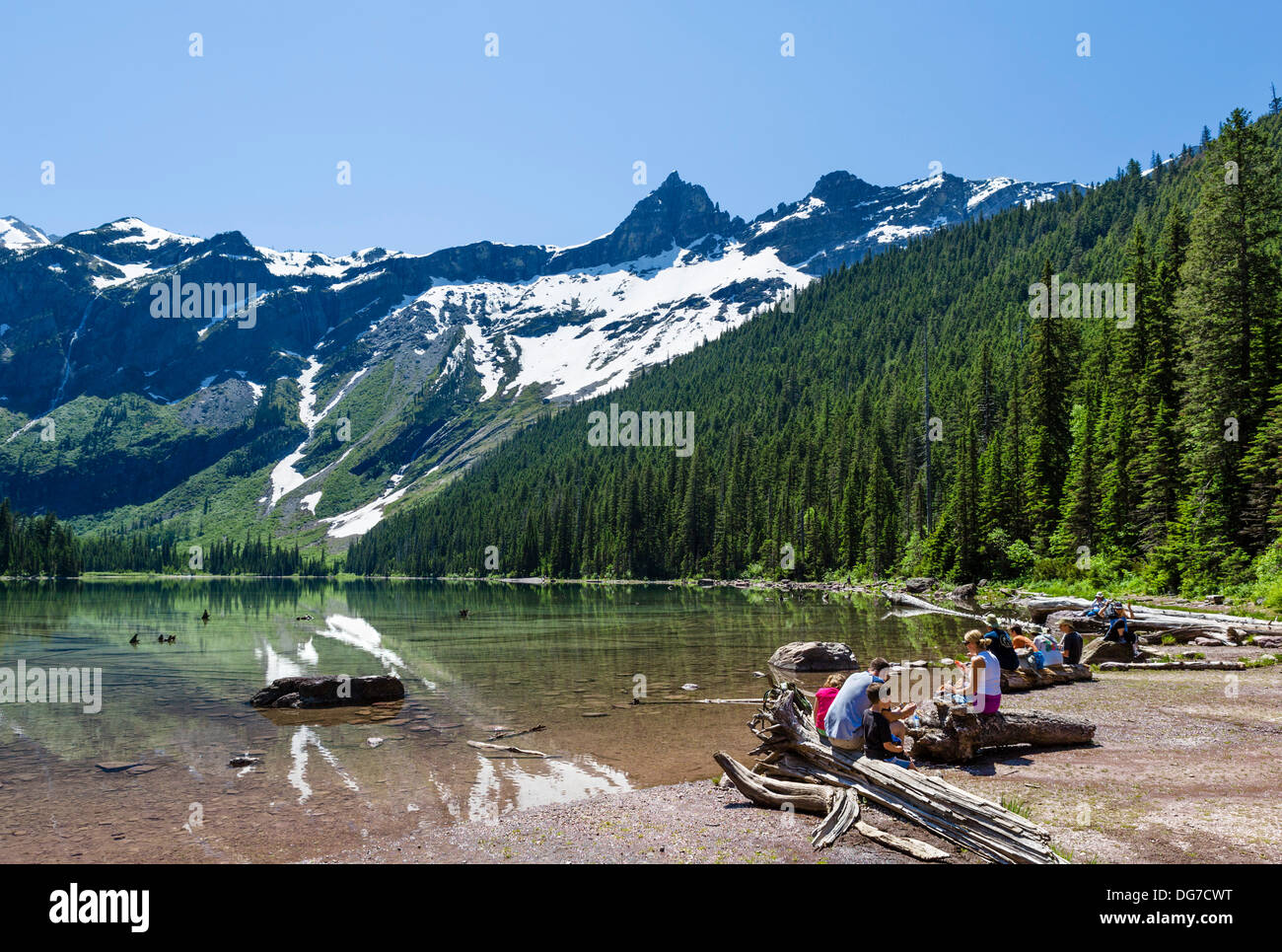 Walkers having a picnic on the shores of Avalanche Lake, Avalanche Lake Trail, Glacier National Park, Montana, USA - Stock Image