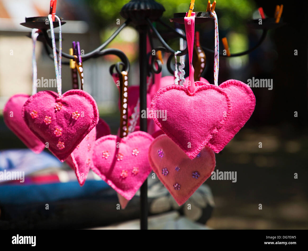 Pink felt pin cushion hearts displayed for sale at a craft market stall. - Stock Image