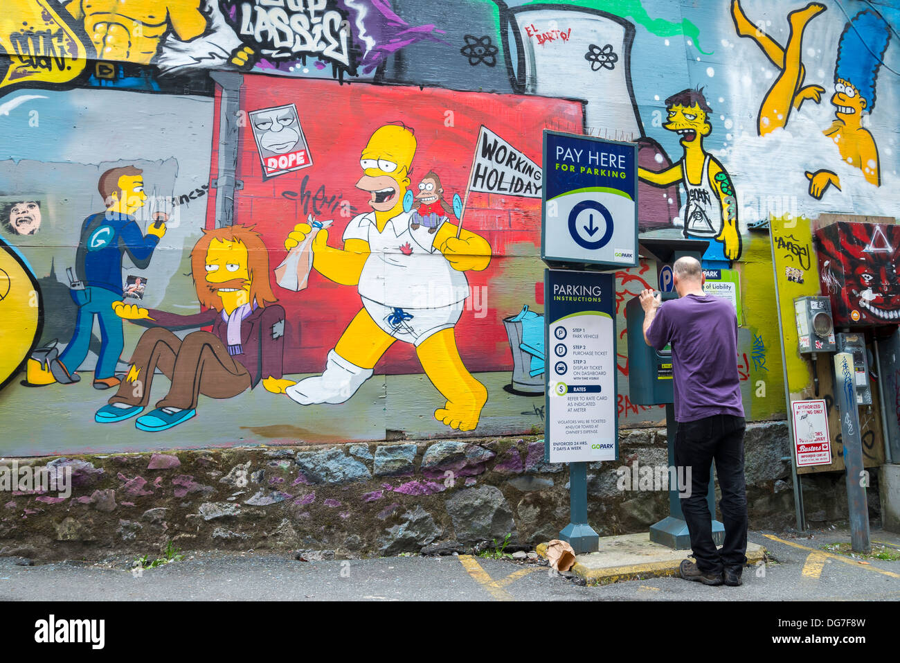 Man purchases parking at lot with Simpsons themed , graffiti style mural, DTES, Vancouver, Britsih Columbia, Canada - Stock Image