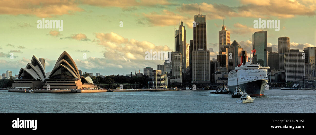 Panoramic view of Sydney Harbor in afternoon light showing the Opera House left of frame with city skyline and the QE2 in port. - Stock Image
