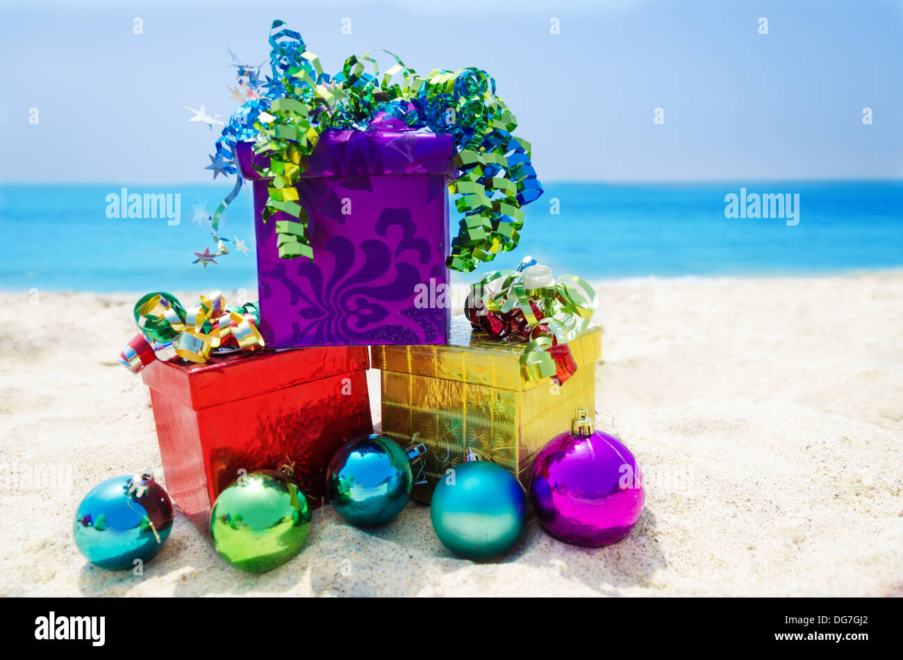 Three Gift boxes with Christmas balls on sandy beach in sunny day ...