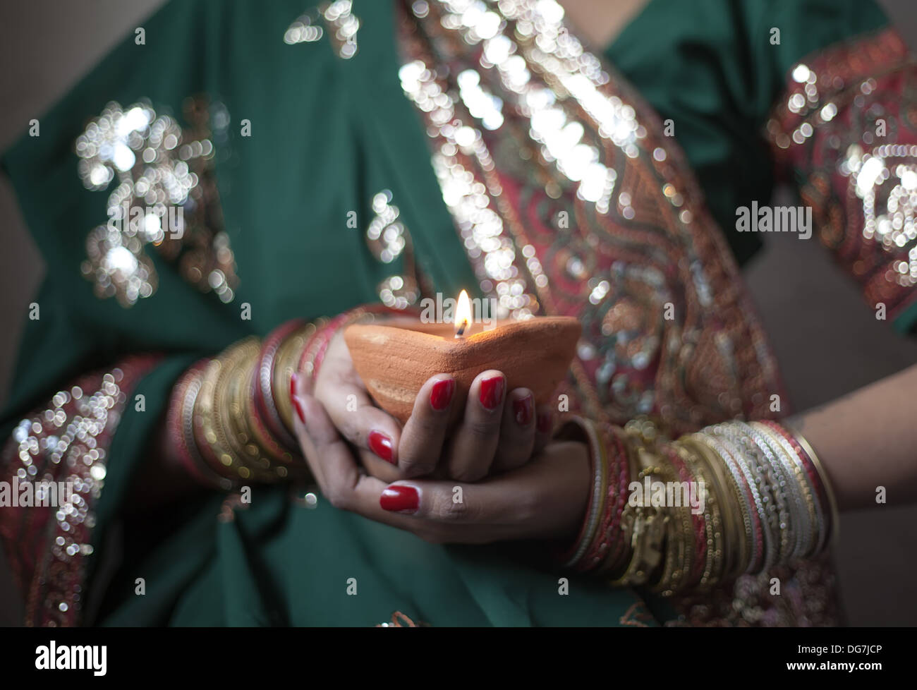 Young woman holding diwali lamp in hands - Stock Image