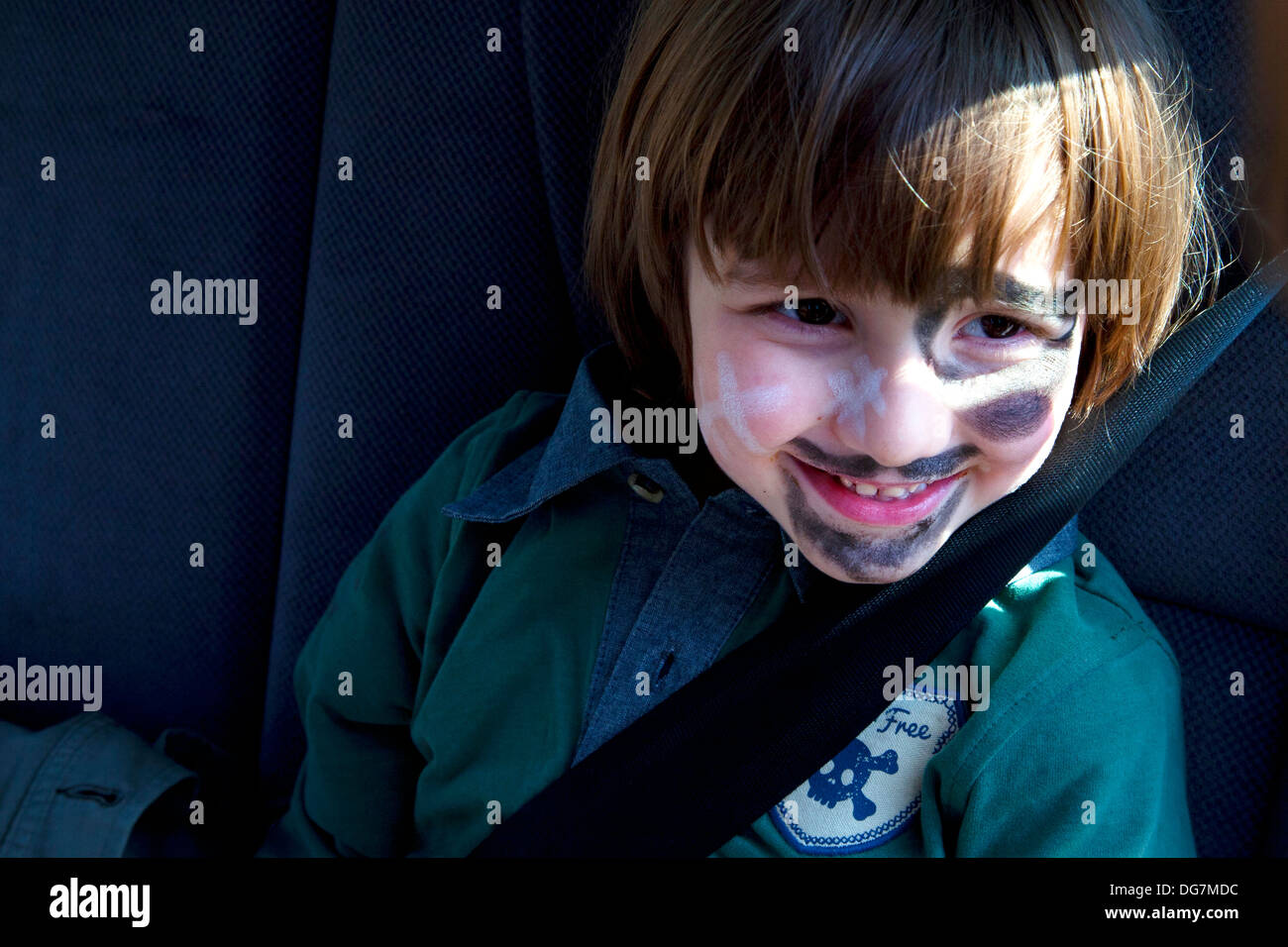 Four and a half year old boy sat in back of car with safety belt on. - Stock Image