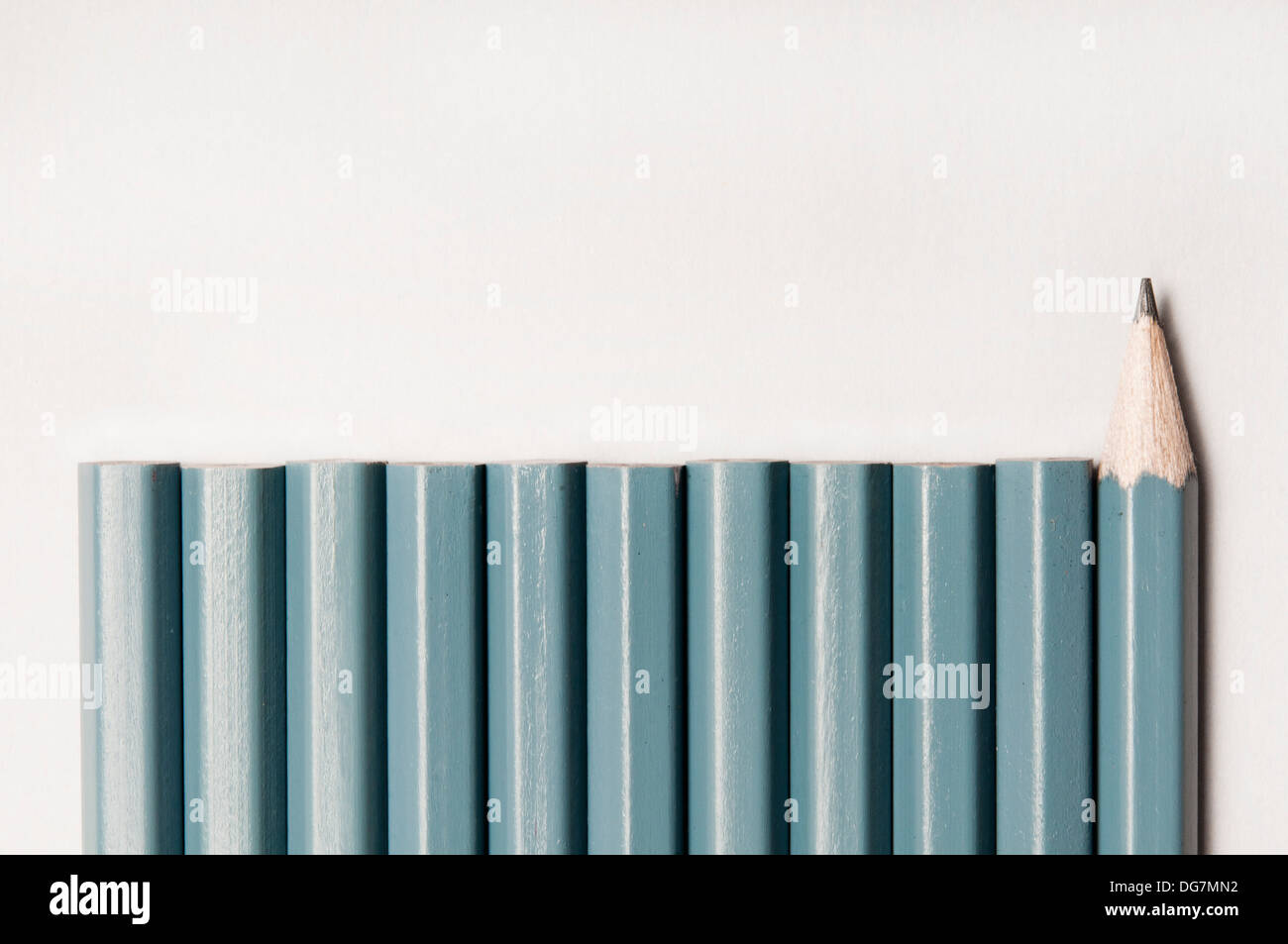 pencils in a row, one turned in the opposite direction, concept for contrarian - Stock Image