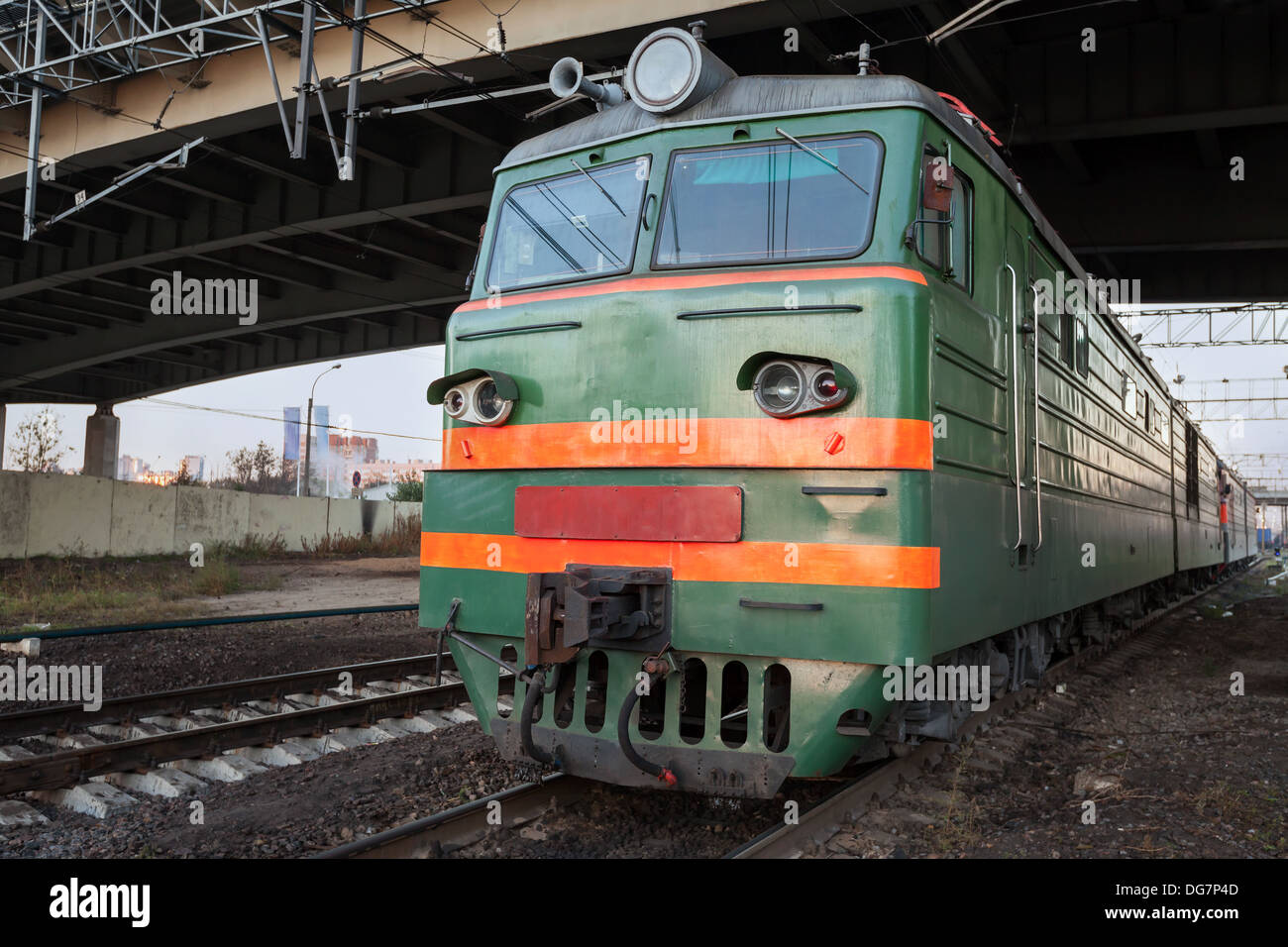 Green locomotive with red stripes on the cabin stands under the bridge on the railway station Stock Photo