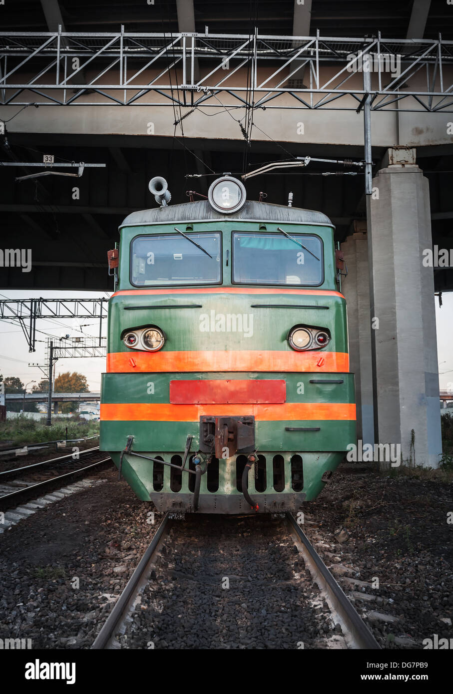 Green locomotive with red stripes on the cabin stands under the bridge on the railway Stock Photo
