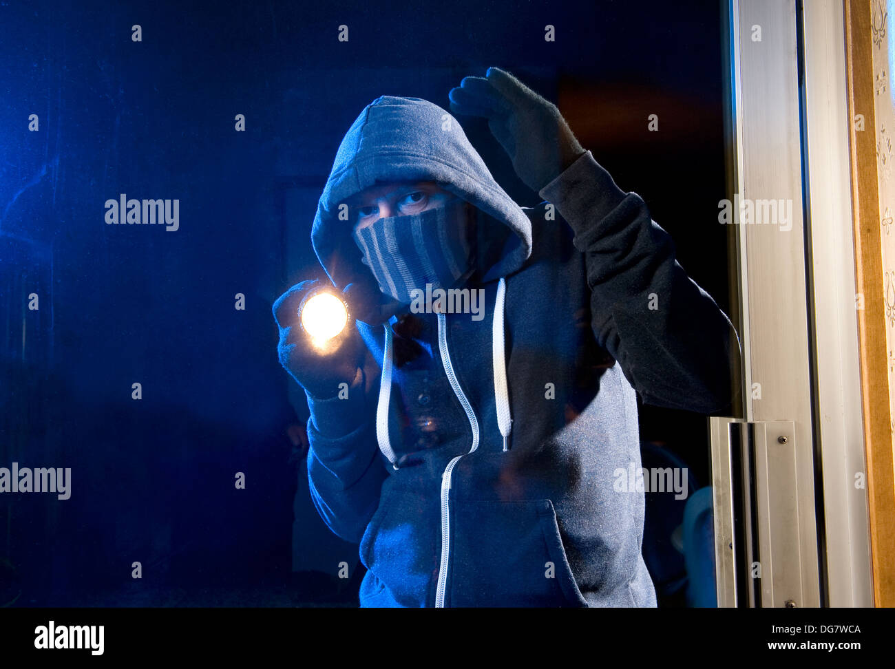 A burglar is looking through the window of a house - Stock Image