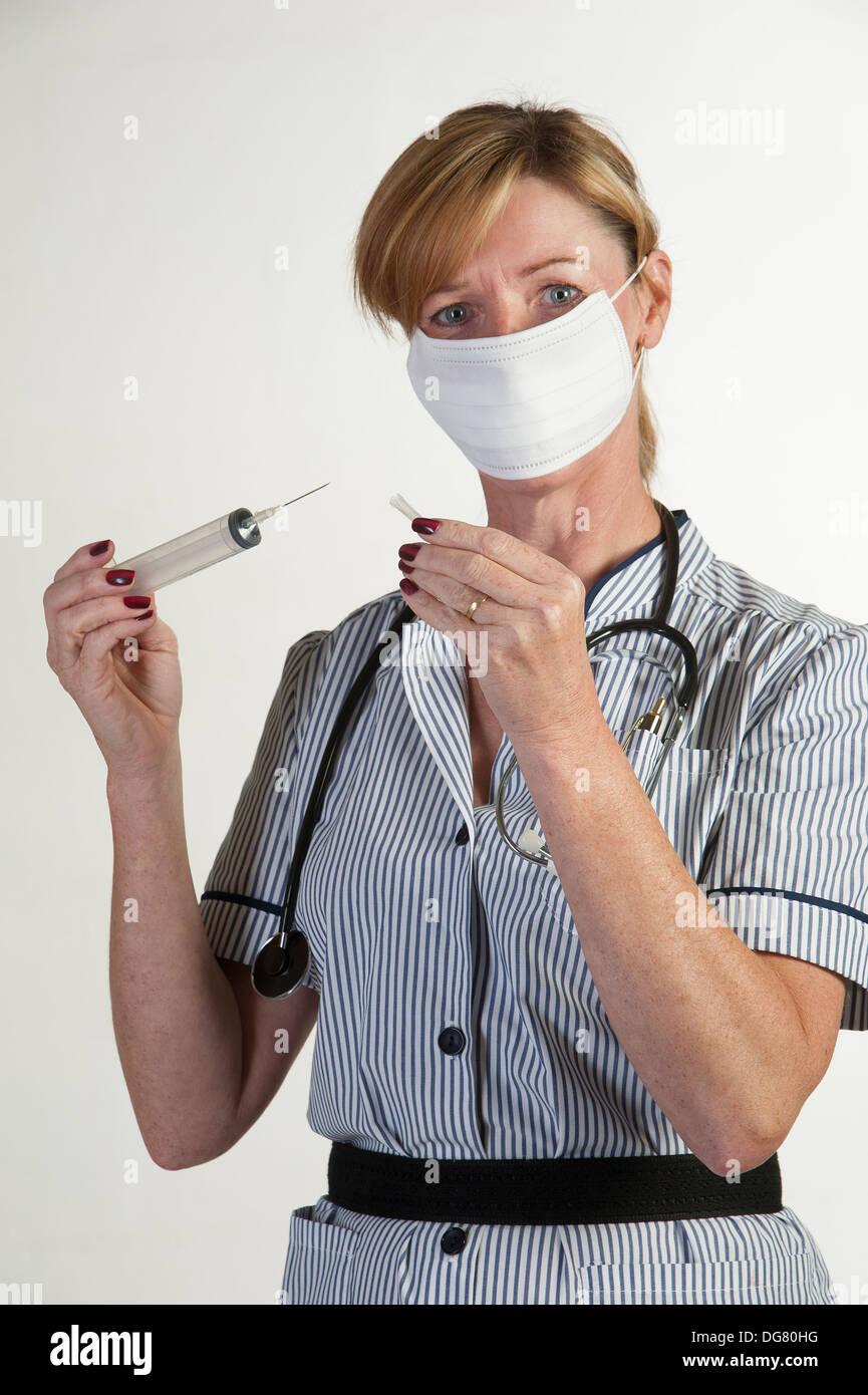 Female nurse holding a large syringe with needle uncovered - Stock Image