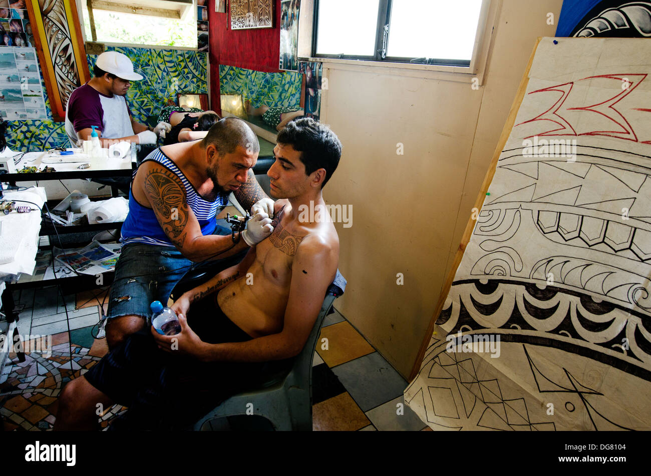 Pacific Island male tattoo artists draws a design on a chest of a young man and woman client s. real people 4 adult in tattoo studio. - Stock Image