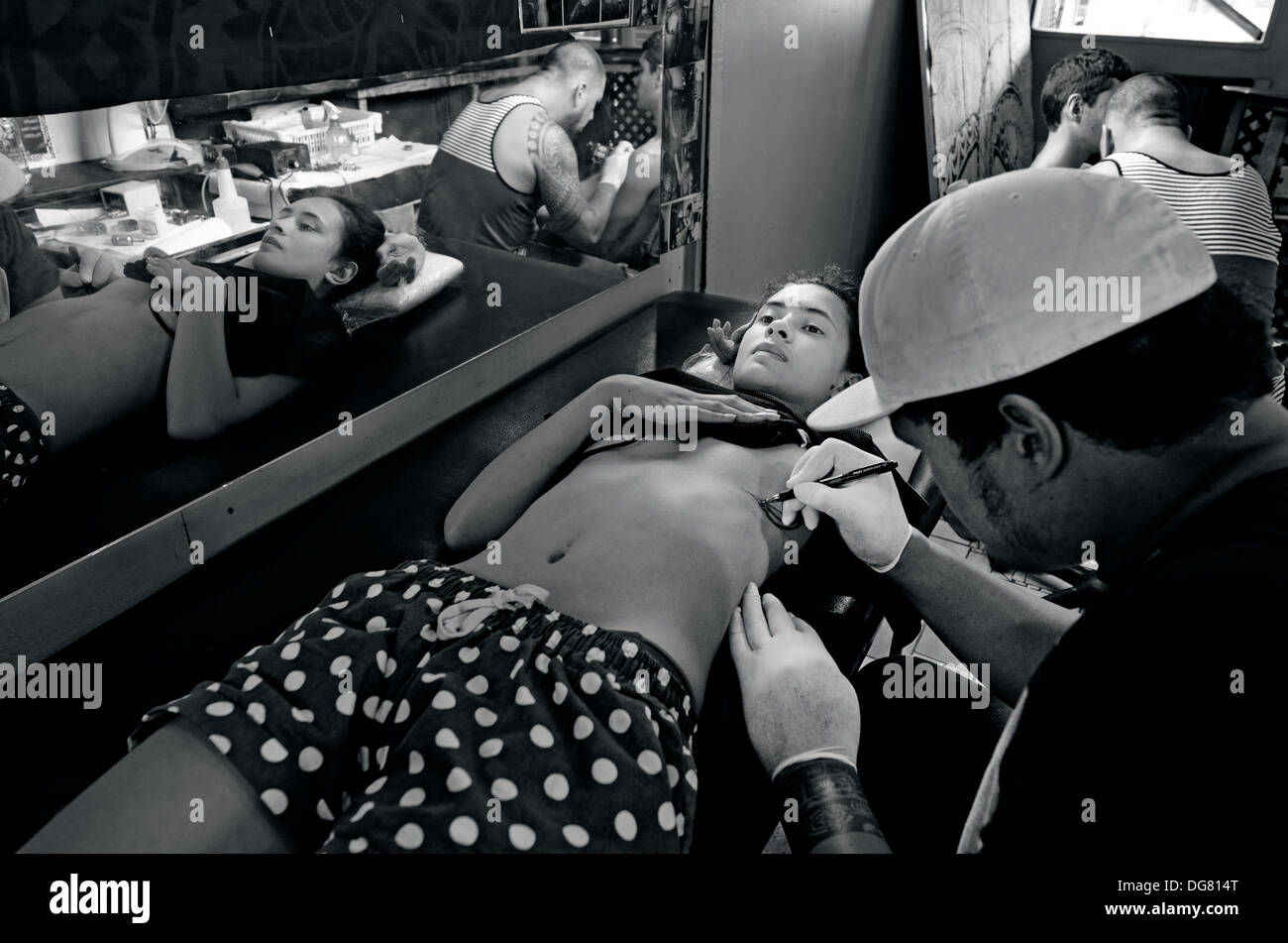 Pacific Island Male tattoo artist draws a design on front of young woman client. real people 2 adult in tattoo studio. (BW) - Stock Image