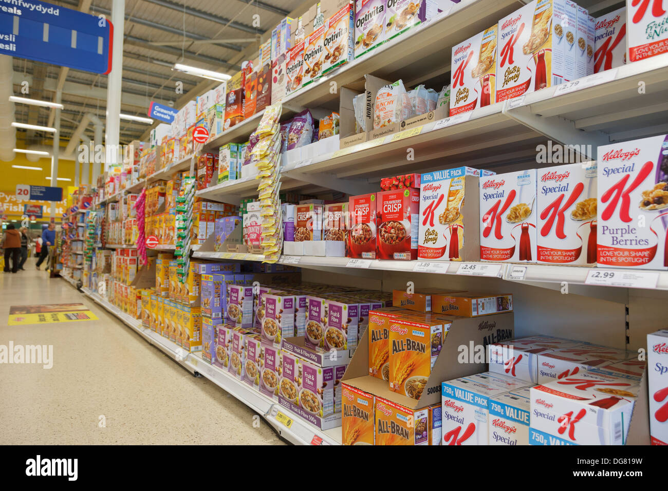 A variety of boxes of own brand and Kellog's breakfast cereals for sale on Tesco's supermarket shelves. UK, Britain - Stock Image