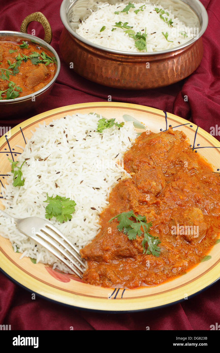 Lamb rogan josh, served with jeera (cumin) rice in beaten copper bowls. - Stock Image