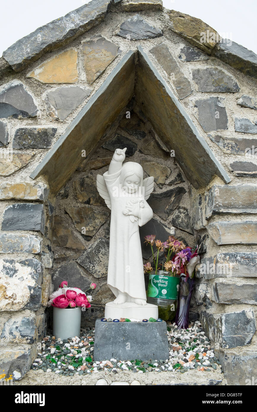 A Christian religious shrine grotto with a little statue of an angel in an Irish cemetery - Stock Image