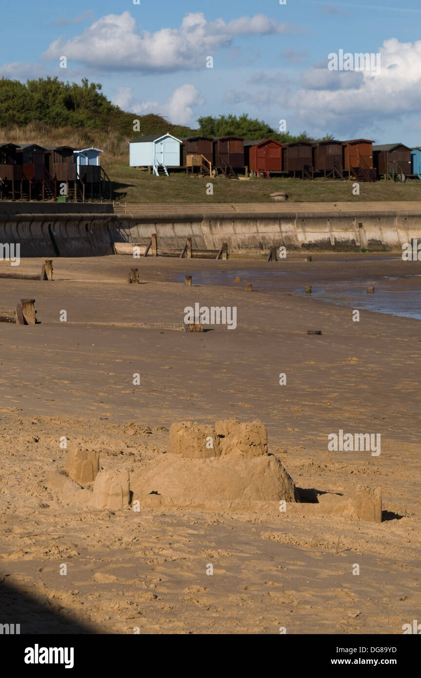 The sun shines on a sand castle completed on Frinton beach . Beach huts stand in the background - Stock Image
