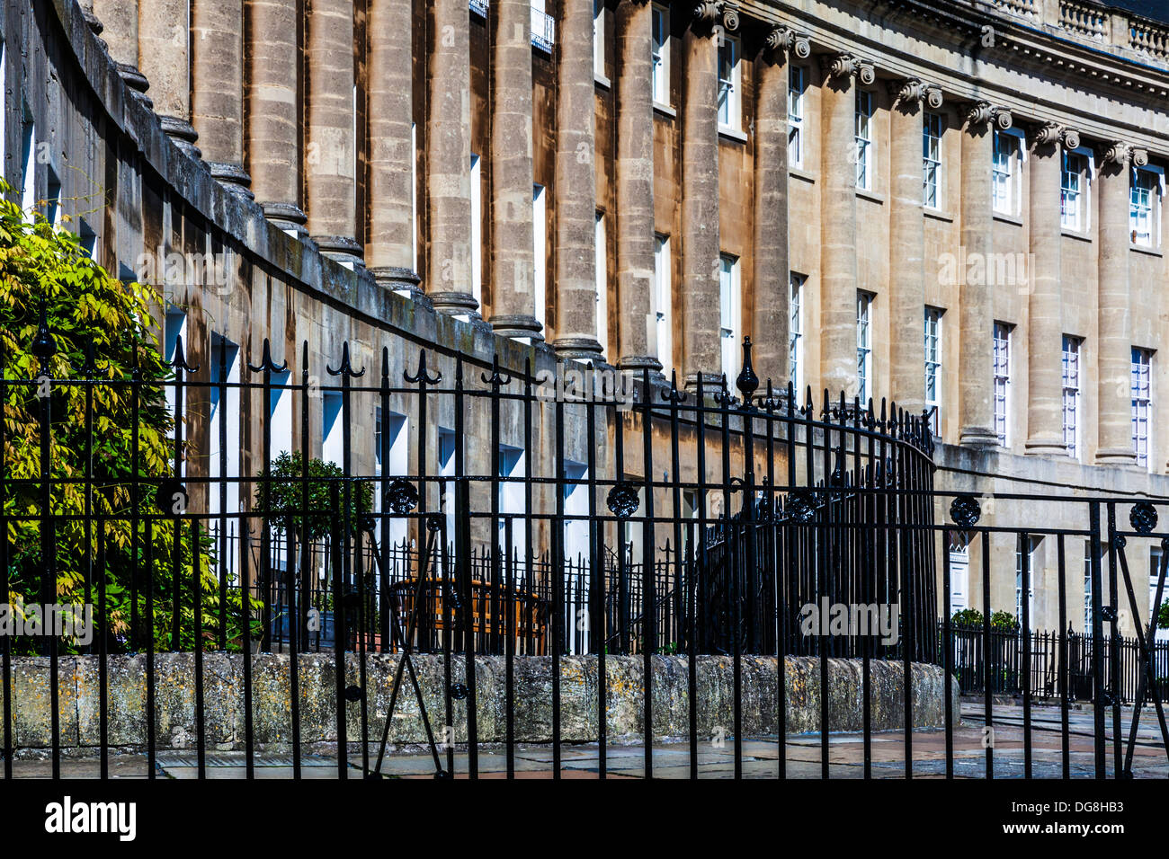 A pattern of wrought iron fence railings in front of the sweeping Georgian facade of terraced houses in The Royal Crescent, Bath - Stock Image