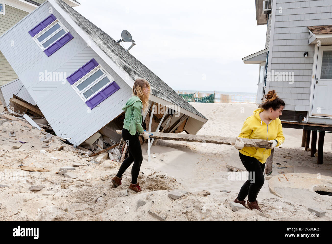 Volunteers cleaning up after a hurricane destroyed a house. A hurricane leaves a path of destruction destroying homes. - Stock Image
