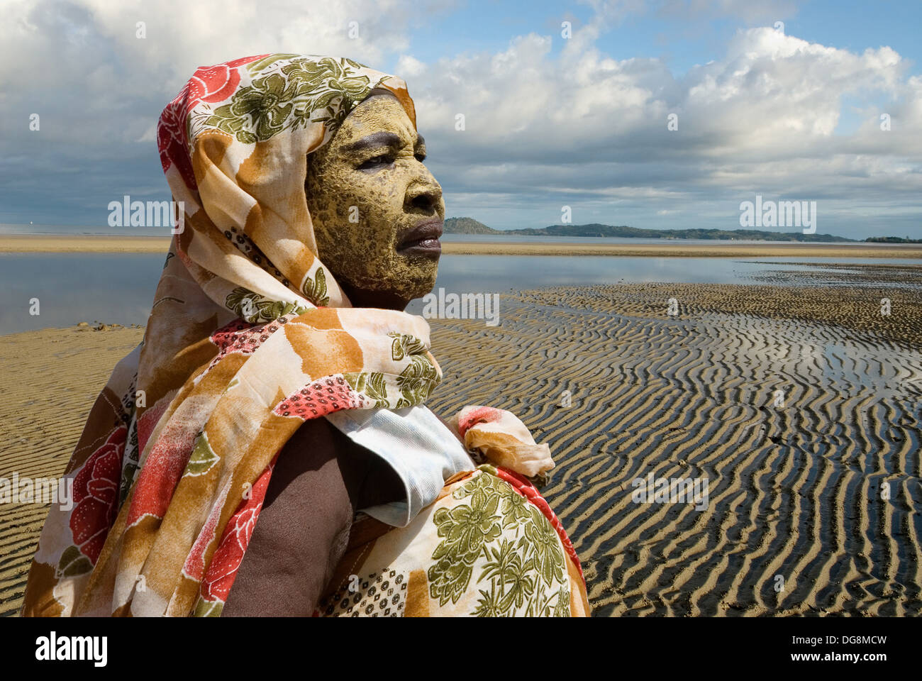 old woman wearing sun protection mask, low tide on the west coast, Nosy Be island, Republic of Madagascar, Indian Ocean - Stock Image