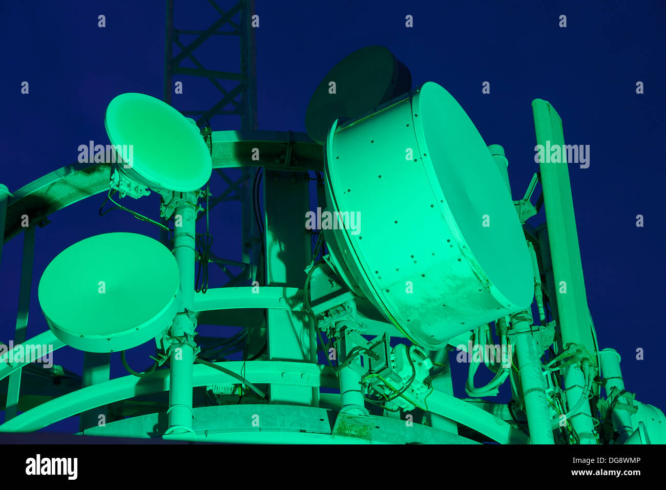 Radio and microwave communication dishes on a transmitter tower at night - Stock Image