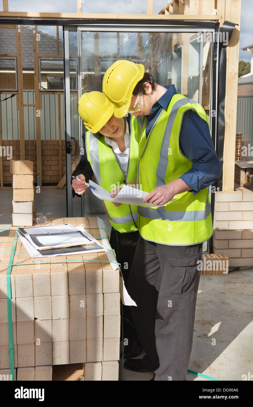 civil engineer and worker discussing issues at the construction site - Stock Image