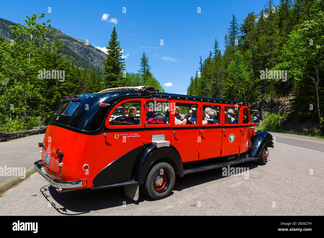 Red Bus Tour in the parking area of McDonald Falls, Glacier National Park, Montana, USA - Stock Image