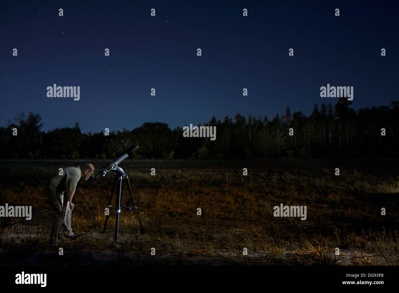 Man with telescope looking at night sky - Stock Image