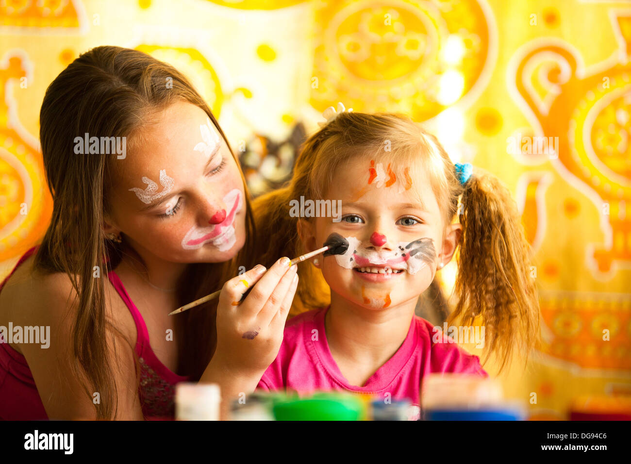 Young sisters playing with painting - Stock Image