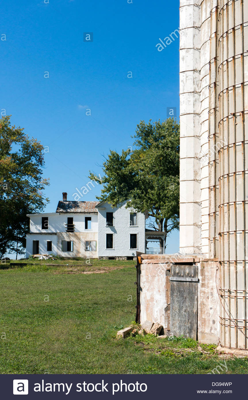 A vacant, gutted farmhouse stands near the farm silo in Rockville, Maryland - Stock Image