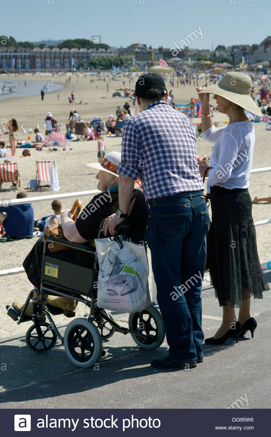 Older woman sat in a wheelchair, together with a younger man and woman all looking at the beach in Weymouth, Dorset, England - Stock Image