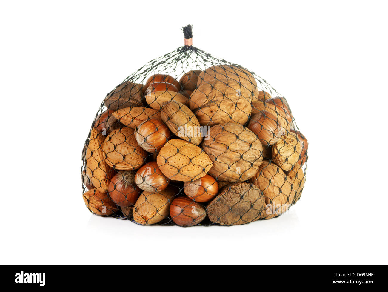 Mixed nuts in a net on a white background - Stock Image